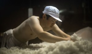 A worker at Ota Brewery in Iga, Mie prefecture on the main island of Honshu, Japan, hjandwashes the rice use in Ota saké. Their sake Hanzo is named after the great ninja Hattori Hanzo.
