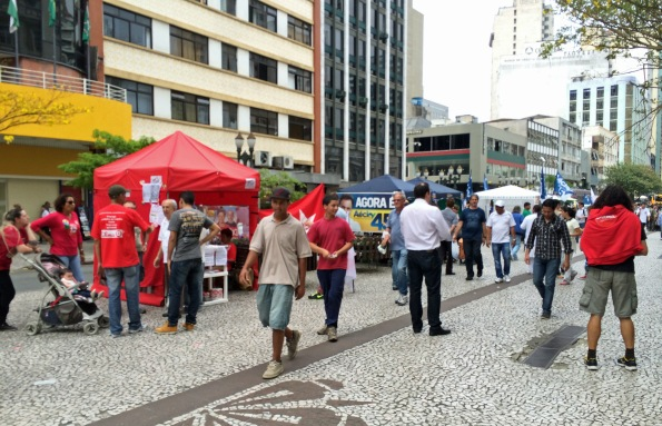 Curitibanos display their political affiliations before the October presidential elections. The red shirts are supporters of incumbent Dilma Rousseff and just behind them are the white tentsand banners of Aécio  Neves' fans.