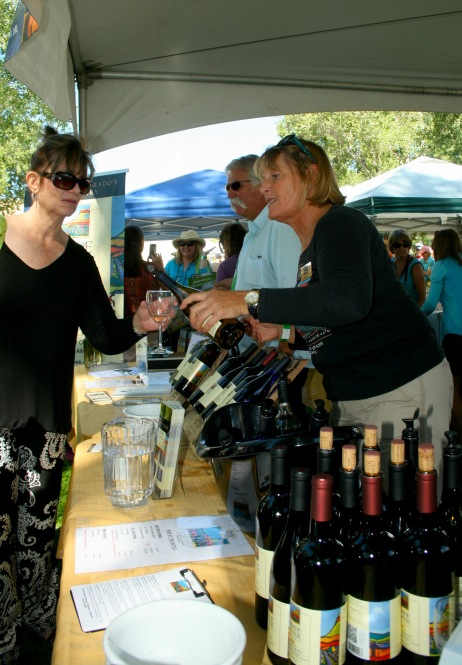 Naomi Smith, right, of Grande River Vineyards pours a glass of wine for one of the 6,000 guests attending Saturday's Festival in the Park at Palisade's Riverbend Park.